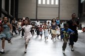 Mixed group of people running towards the camera as part of Residents Day in the Turbine Hall