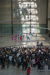a group of dancers perform at the back of the turbine hall