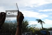 Runa Islam still from CINEMATOGRAPHY image of a pair of hands holding up a transparency to the sky with the text cine