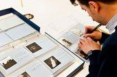 Tate Britain preservation volunteer Aurelio re-numbering Keith Piper photographs