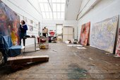 Artist Lucy Stein checks behind one of her big colourful paintings, in the studio