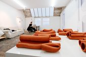 Artist Nicolas Deshayes sits in a corner in front of a copper coloured abstract installation in the studio