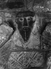 Black and white photograph of a primitive face carved into stone.