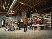 Theaster Gates stands in the center of his workshop surrounded by his assistants