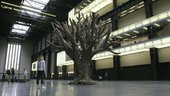 A woman stands in the Turbine Hall and looks up at Ai Weiwei's Tree