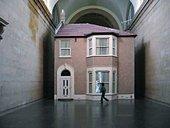 Video still of spectators looking at Michael Landys installation Semi detached at Tate Britain