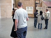 Video still of spectators looking at Michael Landys installation Semi detached at Tate Britain three