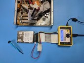 A dismantled computer hard drive, cables and a screwdriver on a blue tabletop