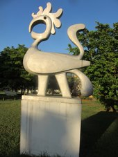 Photograph of an aluminium sculpture of a stylised bird on a square pedestal (on which the title Savacou is inscribed), installed in a park with grass, trees and blue sky in the background