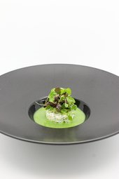 a close up image pea soup food with garnish