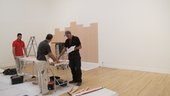 Two people installing an artwork in a gallery, adhering pinkish strips of paper vertically onto the wall