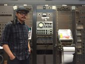 C Spencer Yeh standing in front of an RCA Mark II synthesizer