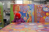 The artist Yayoi Kusama works on one of her large-scale paintings in her studio in Tokyo