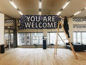 Photograph of Tate Exchange space at Tate Modern with a person up a ladder hanging a banner that reads: you are welcome