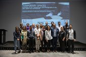 A group photograph of contributors to the 'Temporary Spaces' symposium, posing together in front of a projected slide showing the title of the event