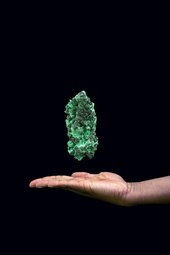 Photograph of a hand with a green precious stone floating above it against a black background