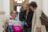 a staff member in a wheelchair shows two visitors a map in Tate Britain