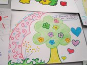 Kids drawing of a tree with flowers and love hearts around it