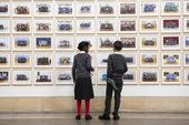 Two people standing looking at Steve McQueen Year 3: a wall lined with school photographs