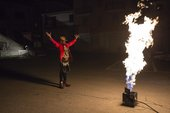 A man with raised hands looks at large flames