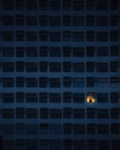 A large block of flats with only one light on and a person standing in the window