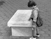 A little girl looks at a marble bench engraved with text