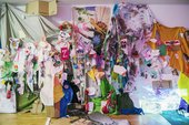 A wall covered in colourful paper and string