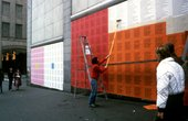 Man pasting Holzer's work onto a wall