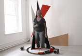 installation shot of some kinetic work with a train set moving around a cut out of a woman holding a gun