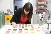 a woman sits and looks at colour swatches