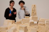 A close up of an arrangement of blocks made out of sand to appear like a city skyline. in the backround and out of focus are two figures.