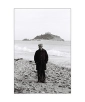 Photo of Khakhar standing on a beach in Cornwall. Fully dressed wearing a cap