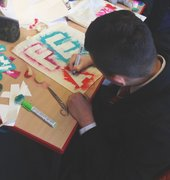Kid stencilling his design onto a bag