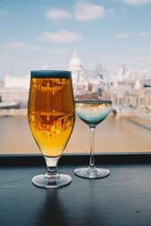 Photograph by Jade Nina Sarkhel of a pint of beer and a glass of white wine in front of window with views of London.