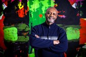 Photograph of a Kerry James Marshall looking at the camera in front of an abstract green and red painting