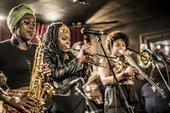 Three members of KOKOROKO playing brass instruments