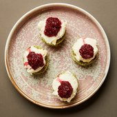matcha scones with whipped cream and raspberries on top