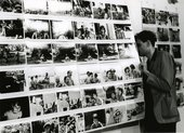a man looks at black and white photographs on display