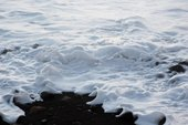 Colour photograph of white waves on a coast