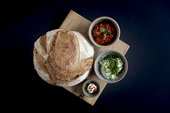 baked bread with whipped butter, roasted red pepper humous and red pepper dip