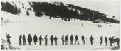 Black-and-white photograph of a line of figures lined up in the snow, some on skis, some talking to each other