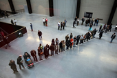 Aerial photograph of a group of people positioned along a white line drawn across the Turbine Hall floor at Tate Modern