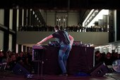 A raised DJ booth in the centre of a large industrial room. The DJ is playing to a large crowd of people.