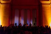 A crowd of people watching a band perform in the Duveen Galleries