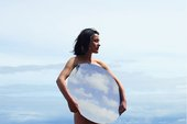 A white woman standing against a blue sky holds a large disk which reflects the background