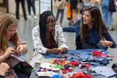 three women sit and sew and make at a table in Tate Britain