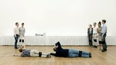 Group of people in white gallery space with two people lying on the ground