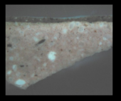 Fig.6 Cross-section through brown paint at the lower left edge, photographed at x260 magnification in ultraviolet light. From the bottom: salmon pink ground; opaque brown paint; varnish
