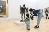 a boy and his mother stand in Tate Britain in front of a sculpture of a figure