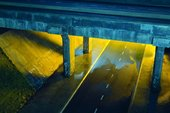 film still from Mark Leckey Dream English Kid, showing concrete bridge over a bypass lit up yellow.